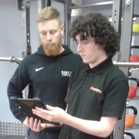 Jamie Ford (L) of Easy St PT gets a quick lesson from Jake Artingstall (R) of Smarter Technologies